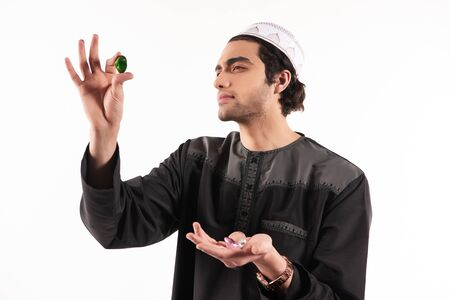 Arab man in ethnic dress looks at precious stones. Jewelry store concept. Isolated on white background. Studio portrait. Stock Photo