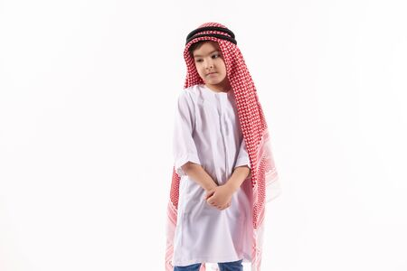 Arabian thoughtful boy in keffiyeh is standing with hands folded. Isolated on white background. Studio portrait.