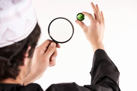 Arab jeweler examines precious stone through magnifying glass. Pawnshop concept. Isolated on white background.