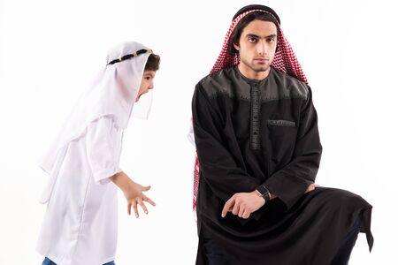 Arab boy screams at adult father in keffiyeh. Isolated on white background. Parenthood concept. 스톡 콘텐츠