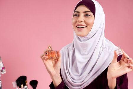 Attractive Arabian woman in hijab uses perfume. Isolated on pink background. Studio portrait.