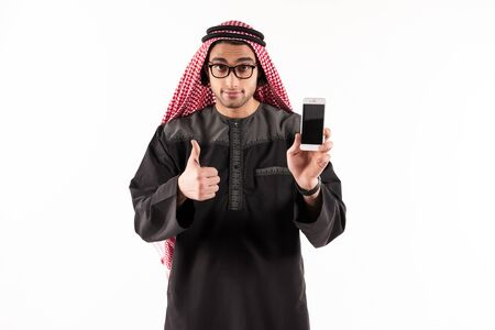 Happy Arab businessman in keffiyeh talks on cellphone and showing thumbs up. Cellular technology concept. Isolated on white background. 스톡 콘텐츠