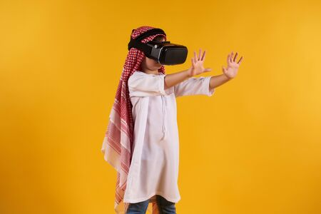 Arabian happy boy with virtual reality glasses plays interactive game. Future technology concept. Isolated on yellow background.