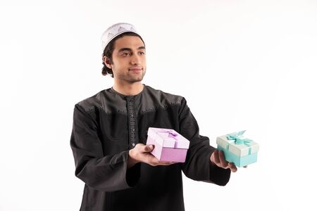 Arab man holds in hands two gift boxes. Isolated on white background. Studio portrait. 스톡 콘텐츠