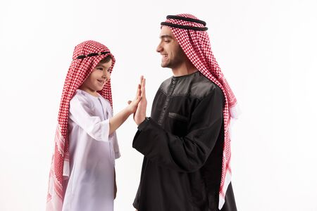 Arab happy father gives five little sons in national attire. Isolated on white background. Parenthood concept. 스톡 콘텐츠