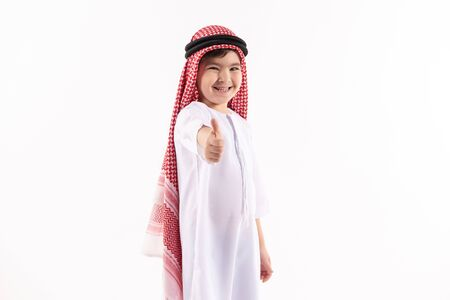 Arab boy in keffiyeh shows thumbs up. Isolated on white background. Studio portrait. 스톡 콘텐츠