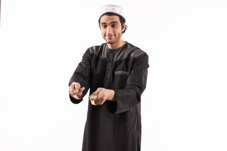 Arab male in ethnic dress offers gold watch. Moneylender concept. Isolated on white background. Studio portrait.