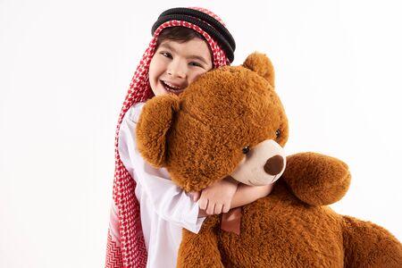 Arabian happy boy in keffiyeh hugs stuffed toy. Childhood concept. Isolated on white background. 스톡 콘텐츠