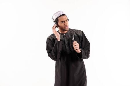 Arab male in ethnic dress is singing in karaoke. Isolated on white background. Studio portrait.