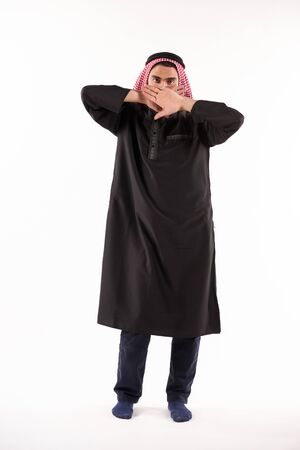 Arab man in keffiyeh covers mouth with hands. Overall silence concept. Isolated on white background.