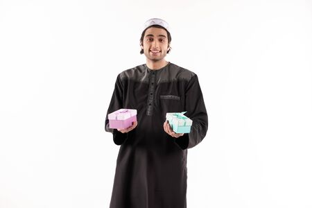 Arab man holds in hands two gift boxes. Isolated on white background. Studio portrait.