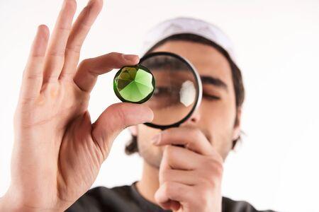 Bijoutier arabe examine la pierre précieuse à travers une loupe. Concept de prêteur sur gages. Isolé sur fond blanc.