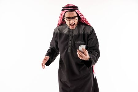 Angry Arab businessman in keffiyeh screams on cell phone. Concept of aggression in work. Isolated on white background.