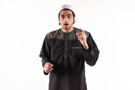 Arab man in ethnic clothes is aware of something. Inspiration concept. Isolated on white background. Studio portrait.