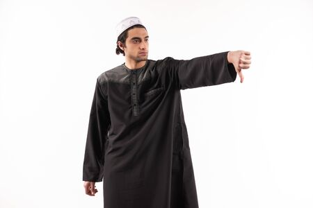Happy Arab man in ethnic clothes shows thumb down. Isolated on white background. Studio portrait. 스톡 콘텐츠
