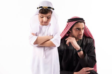 Arab adult man in keffiyeh in quarrel with son. Parenthood concept. Isolated on white background. 스톡 콘텐츠