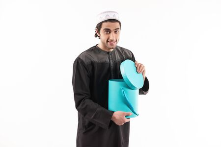 Arab man in ethnic clothes looks in blue box. Isolated on white background. Studio portrait.