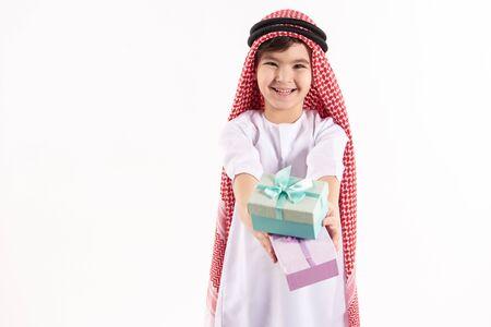 Arabian happy boy in keffiyeh presents gift boxes. Isolated on white background. Studio portrait.