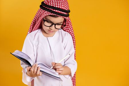 Arab happy boy with glasses makes notes in notebook. Children education concept. Isolated on yellow background. 스톡 콘텐츠