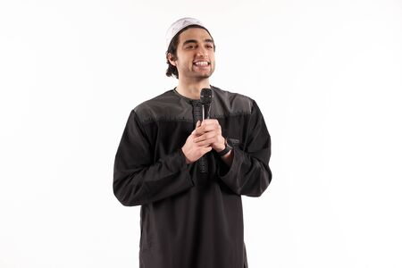 Arab man in ethnic attire stands with microphone. Isolated on white background. Studio portrait. 스톡 콘텐츠