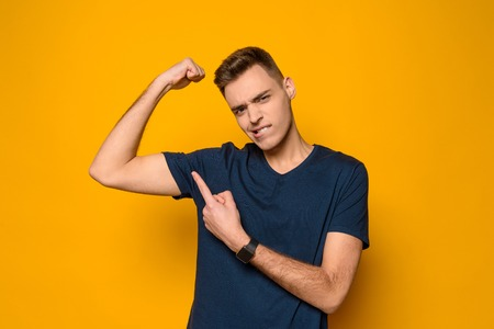 Young thin handsome guy shows on biceps of arm isolated on yellow background. Strength. Studio portrait. Banque d'images
