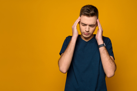 Young lean guy tries to remember something isolated on yellow background. Studio portrait. Male emotions.