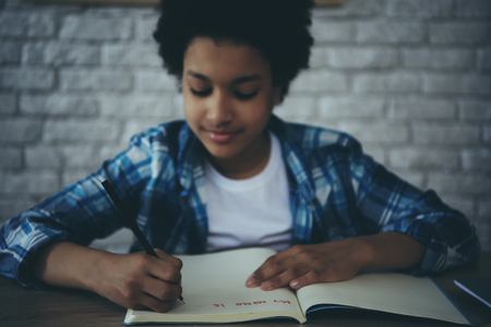 African American little preschooler doing homework sitting at table. Child education concept.