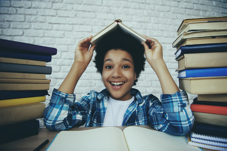 African American schoolboy holds book over head among pile of books, doing homework. Child education concept.