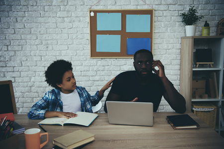 African American boy distracts father from work when does homework at home. Child education concept. Fatherhood. Banco de Imagens