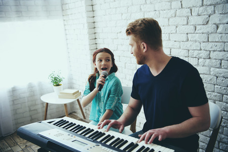 Single father plays on synthesizer while daughter sings song into microphone. Accompaniment. Fatherhood.