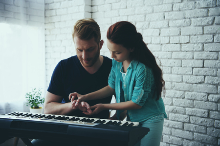 Talented girl teaches redheaded father playing synthesizer. Fatherhood. Child education concept. 写真素材 - 103056313