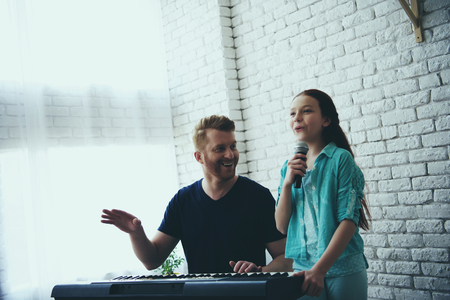 Single father plays on synthesizer while daughter sings song into microphone. Accompaniment. Fatherhood. 写真素材 - 103212528