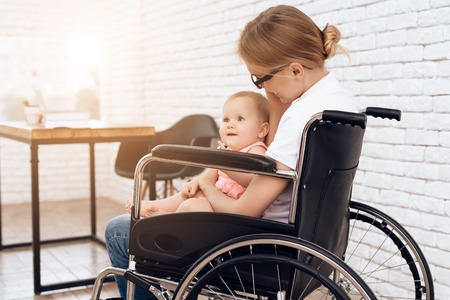 Disabled mother in wheelchair with newborn baby. Disabled, motherhood concept.