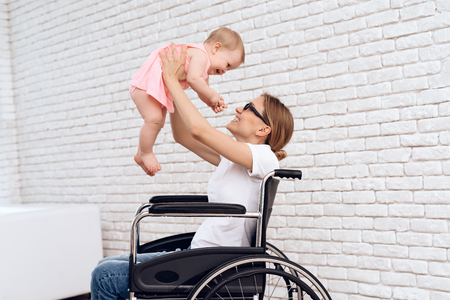 Mother in wheelchair play with newborn baby. Disabled, motherhood concept.