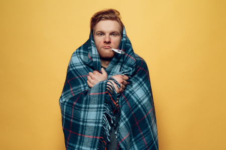 Guy Wrapped in Plaid with Thermometer in Mouth. Sick Guy in Checkered Blue Wrap has cold. Ill Handsome Person Feels Uncomfortably Unhealthy Isolated on Yellow Background. Concept of Cold Archivio Fotografico