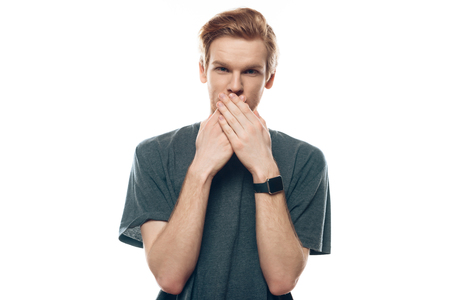 Portrait Shocked young man covering mouth with hand. Surprised Guy in Casual Shirt. Adult Person Looked Speechless. Concept of Human Emotions Isolated on White Background.