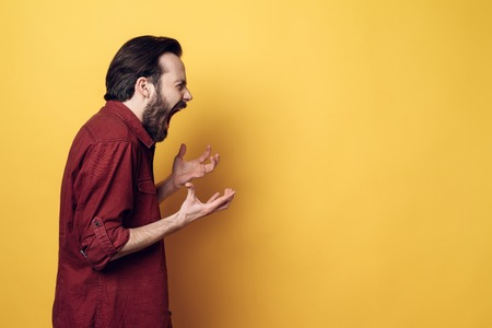 Portrait of Screaming Frustrated Angry Man. Guy Hands up and Screaming. Furious Guy with Hipster Haircut Isolated on Yellow Background. Adult Person Looked Evil. Concept of People Emotions