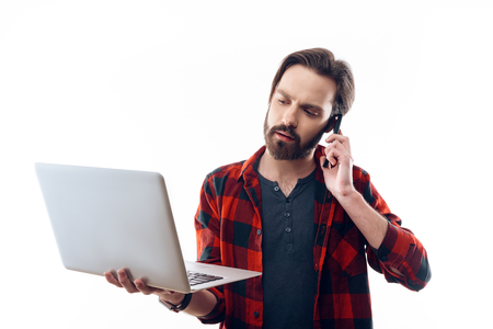 Bearded Man Working on Laptop and Talking on Phone. Sad Guy in Red Checkered Shirt Using Light Laptop Looks Like Doing Serious Work . Isolated on White Background. Concept of People Emotions Stock Photo