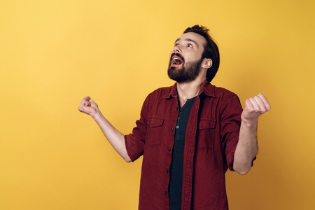 Excited Attractive Bearded Man Clenching Fists. Young Excited Guy in Casual Red Shirt Isolated on Yellow Background. Attractive Person in Astonishment. Concept of People Emotions. Stockfoto