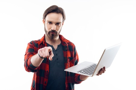 Guy Holds Laptop and Points Finger Towards Camera. Serious Bearded Confident Man looking at camera with amazed expression. Isolated on White Background. Concept of People Emotions