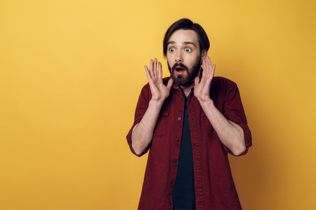 Portrait of Shocked Bearded Man keeps Hands up. Surprised Guy with Hipster Haircut Isolated on Yellow Background. Adult Person Looked in Astonishment. Concept of People Emotions