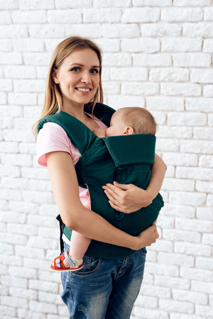 Smiling mother with newborn baby in baby sling. Motherhood concept.