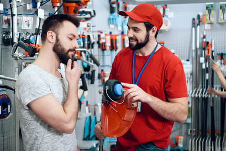 Salesman in red shirt and baseball cap is showing bearded client new lawn mower in power tools store. Archivio Fotografico