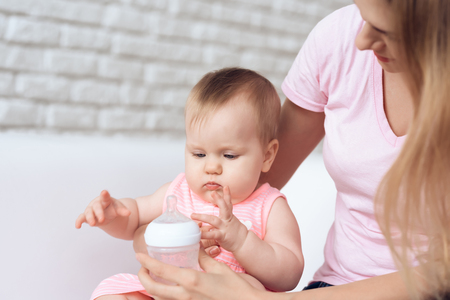 Mother try to feeding baby milk bottle home. Motherhood concept.