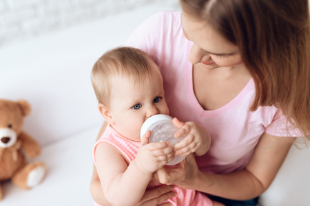 Young mother feeding baby milk bottle home. Motherhood concept. 스톡 콘텐츠