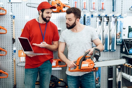 Salesman in red shirt and baseball cap is showing bearded client new chainsaw explaining details on laptop in power tools store. Фото со стока