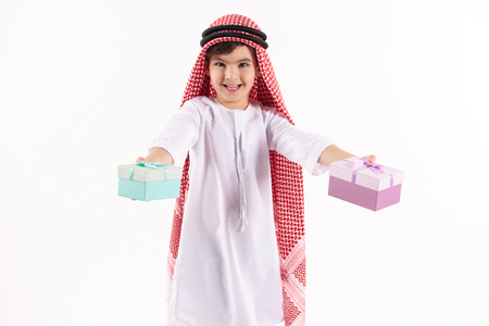 Arabian happy boy in keffiyeh presents gift boxes. Isolated on white background. Studio portrait.