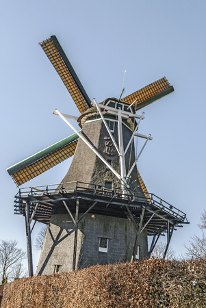 dutch corn windmill on top of a hill against a blue sky background