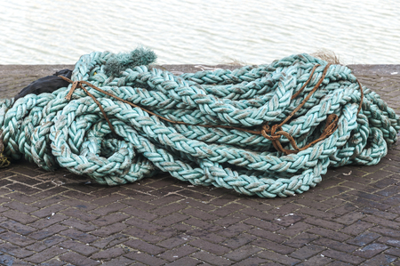 thick rope cables lie on the quay of the harbor