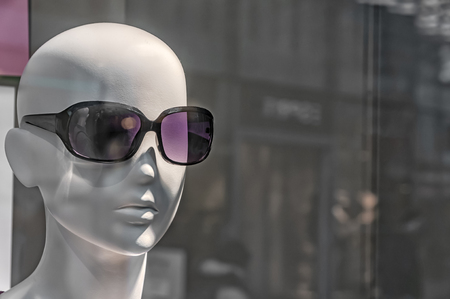 bald head of a mannequin with sunglasses on